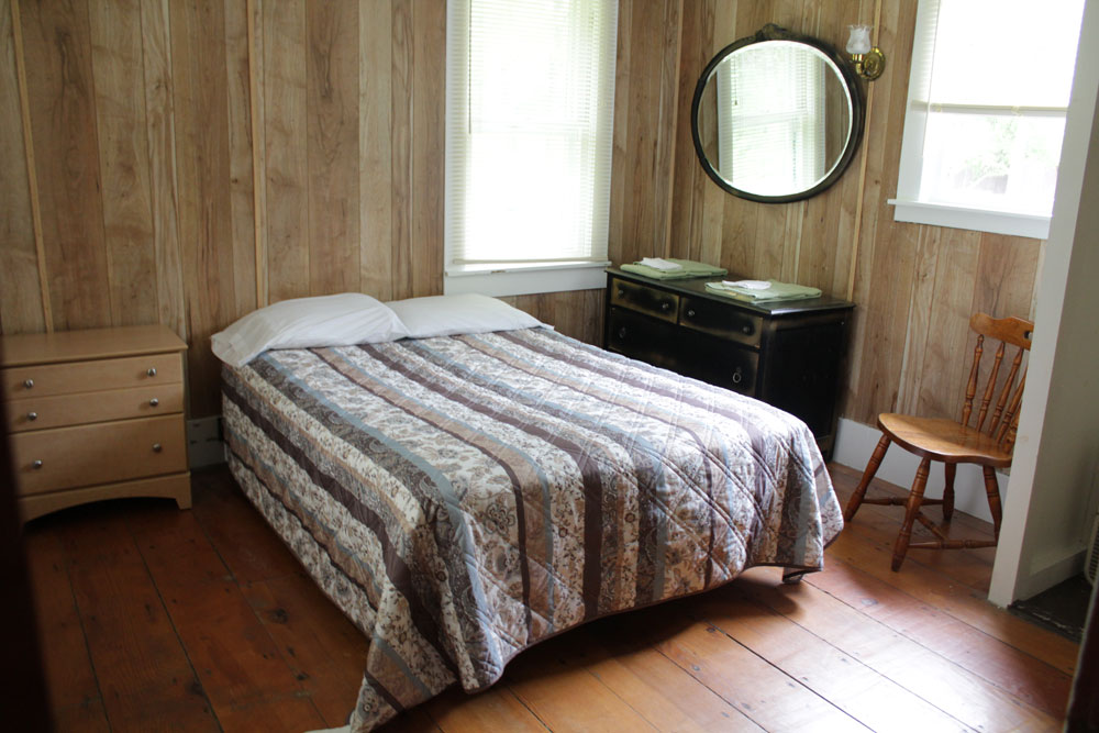 Bedroom with bed and wood paneling