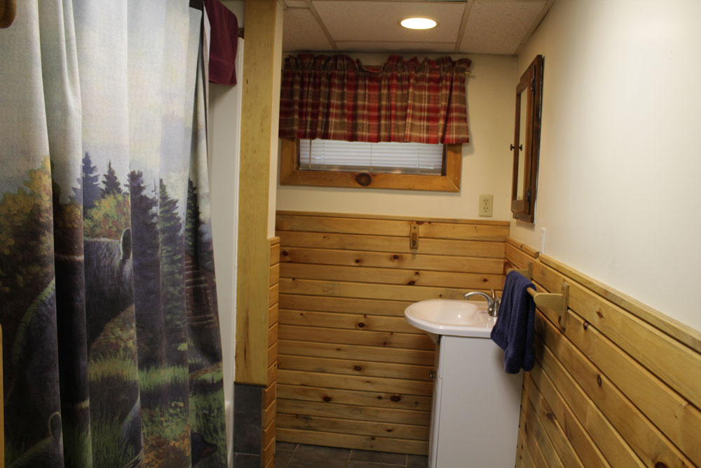 bathroom with shower and sink with wood walls