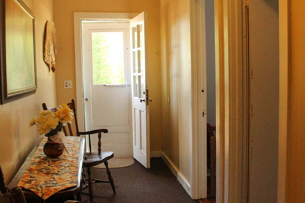 hallway with side table and chair with door leading outside