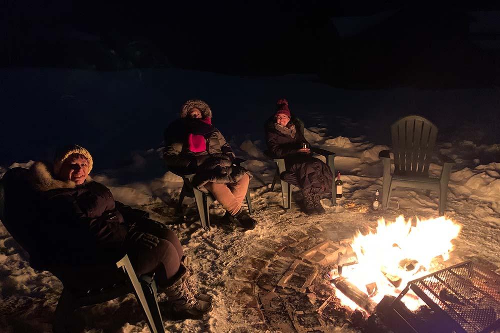 3 people sitting around firepit