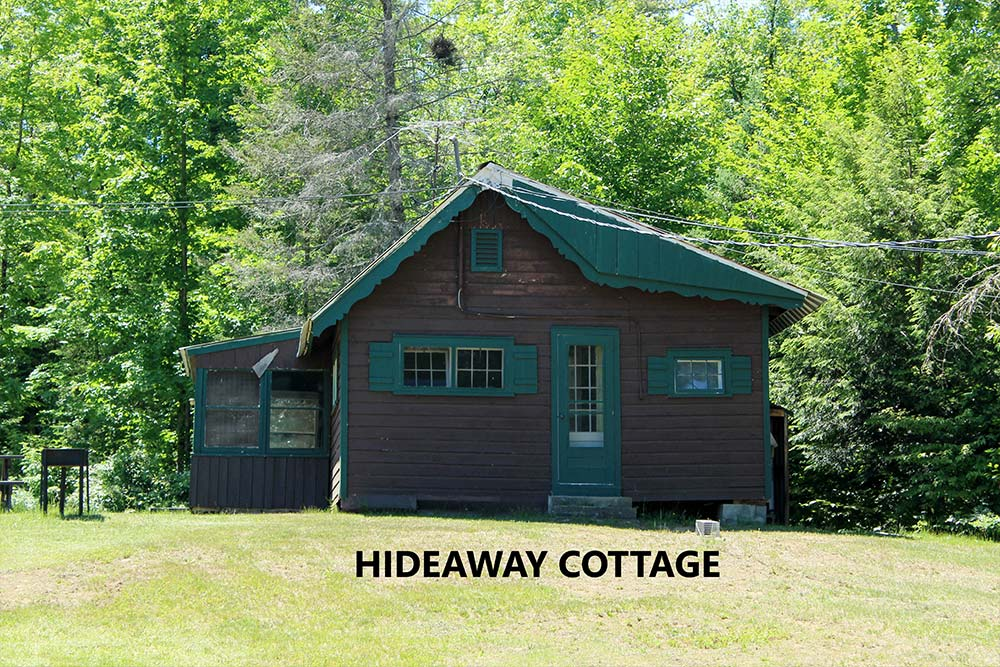 Cottage with brown siding and green trim